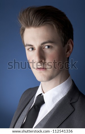 A portrait of a handsome, young man, wearing a suit, against a blue background.