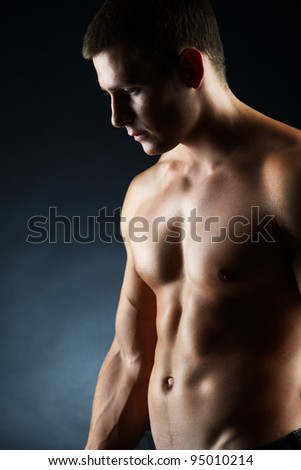 A portrait of a handsome young man without a shirt against dark background