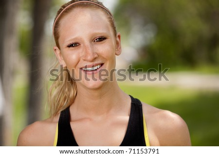 A portrait of a happy female jogger smiling at the camera