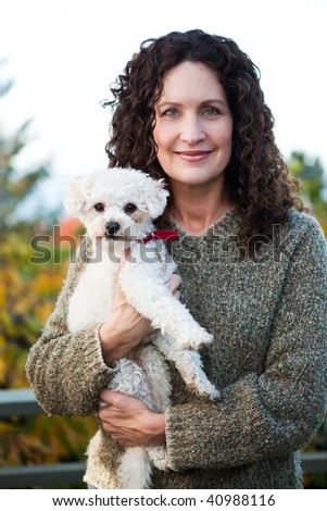 A portrait of a happy mature woman with her dog outdoor