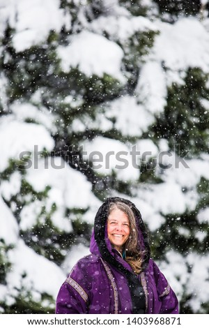 A portrait of a happy middle aged woman in a snowy Colorado, USA
