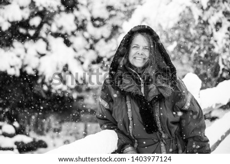 A portrait of a happy middle aged woman wearing a hooded jacket in a wintery Colorado, USA