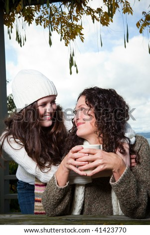 A portrait of a happy mother and daughter drinking coffee outdoor
