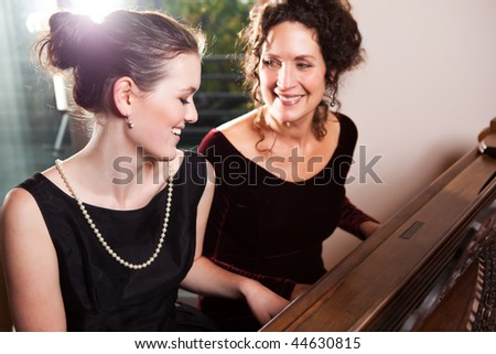 A portrait of a happy mother and daughter playing piano together - stock photo