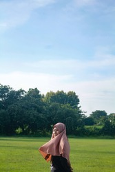 a portrait of a hijab Muslim woman standing on green grass. woman on nature.