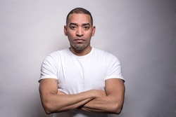 A portrait of a Hispanic middle age athletic man in a white t-shirt, serious, crossed hands, isolated on the grey background