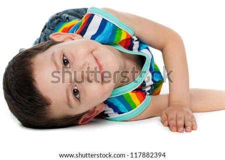 A portrait of a joyful little boy on the floor; on the white background