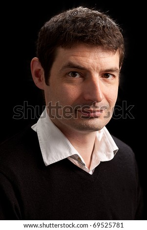 A portrait of a let thirties male.  The model is wearing a white shirt and black jumper/sweater.