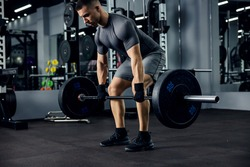 A portrait of a male weightlifter in grey sportswear. He does barbell fitness workout in the modern gym. Weightlifting, power lifting training, sports lover