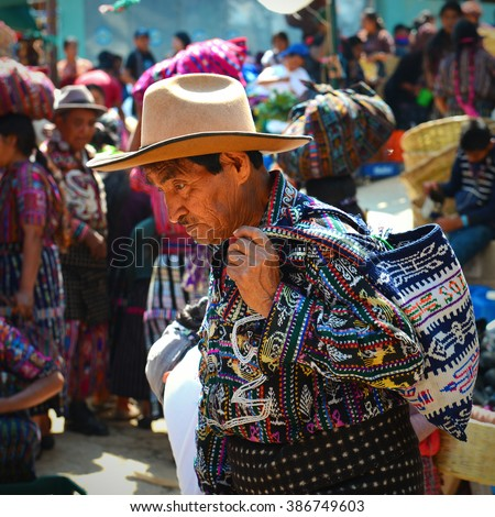 A portrait of a man in traditional clothing on the market of Solola with maya people in the background buying and selling goods, Guatemala.