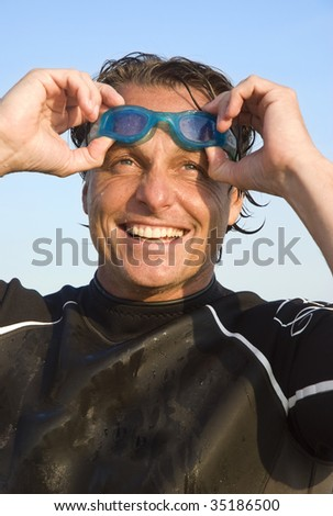 A portrait of a mature triathlete wearing a wetsuit and swimming goggles.