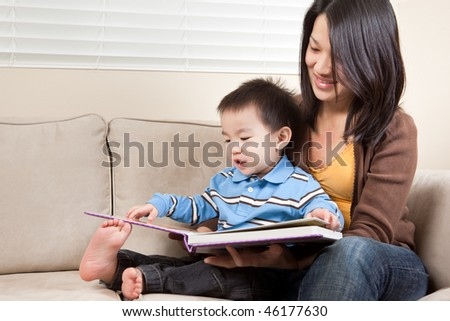 A portrait of a mother and a son reading a book - stock photo