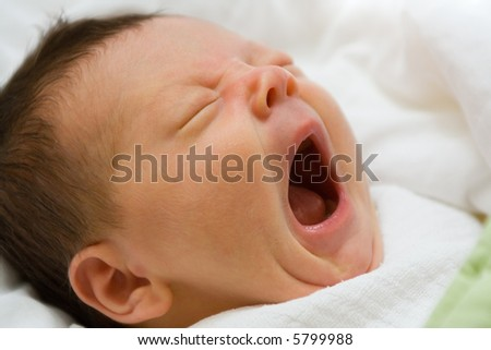 A portrait of a newborn infant girl with her mouth wide open in a big yawn.