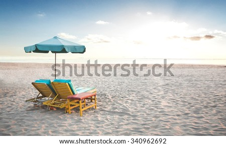 A portrait of a pair of beach chair with umbrella in a seashore