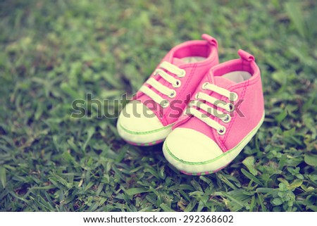 A portrait of a pair pink sneakers toddler shoes on the grass yard, nature background concept #292368602