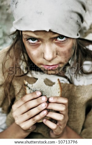 A portrait of a poor beggar child with a piece of bread in her hands. Please check for more. - stock photo