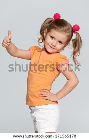A portrait of a pretty smiling girl in orange blouse holding her thumb up on the grey background