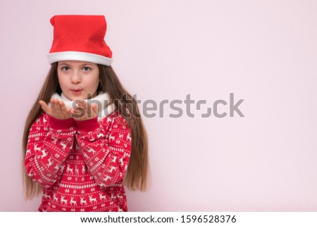A portrait of a pretty young girl, girl blowing on her palms