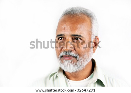 A portrait of a senior Indian man on a white background.