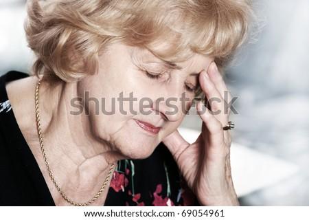 A portrait of a senior lady having headache over dark background