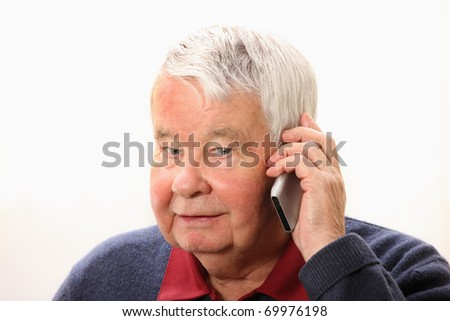 A portrait of a senior man talking on the phone against white background
