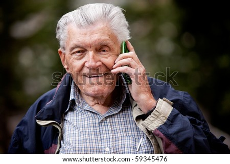 A portrait of a senior using a cell phone outdoors
