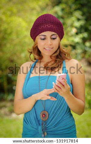 A portrait of a smiling beautiful woman texting with her phone