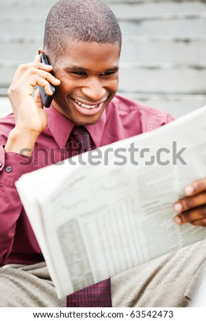A portrait of a smiling black businessman reading newspaper outdoor