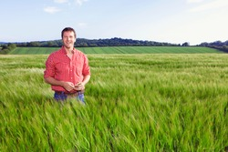 A portrait of a smiling farmer standing in a barley field