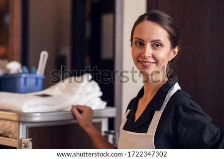 A portrait of a smiling hotel maid with a cleaning cart and clea Сток-фото ©