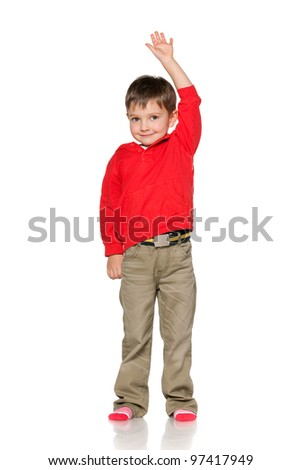 A portrait of a smiling little boy holding his hand up; isolated on the white background