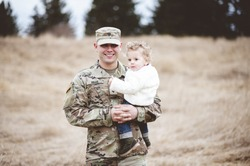 A portrait of a soldier father holding his son in a field