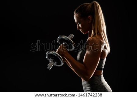 A portrait of a sporty young woman posing with dumbbells over the black background. Beauty, health, sport.