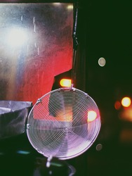 A portrait of a street vendor after the rain, which is illuminated by vehicle lights