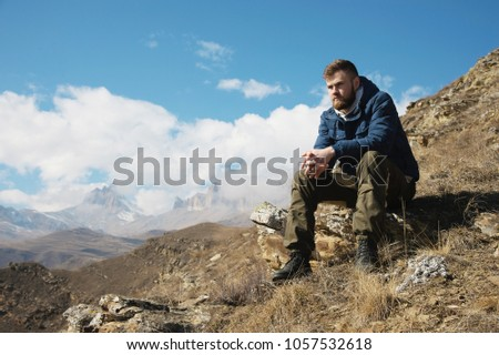 A portrait of a stylish bearded hipster sitting on a rock against the backdrop of epic rocks and contemplating into the distance thinking about life. The concept of tranquility and solitude with