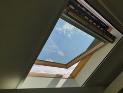 A portrait of a tilted glass sky window taken from the inside of a house. the roof window is a bit open and it has uv protection dur to the different colored skies.