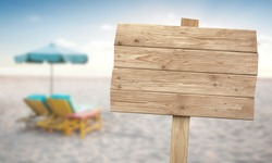 A portrait of a vintage rustic wooden sign on the beach