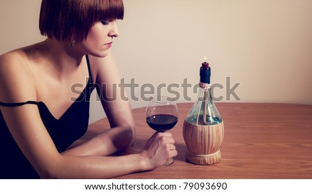 A portrait of a woman drinking wine alone by candlelight.