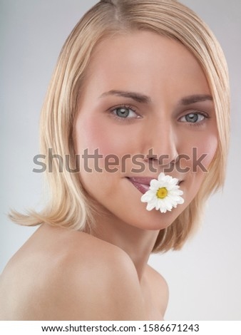 A portrait of a woman with a daisy in her mouth
