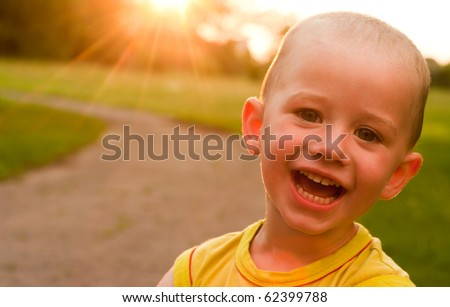 A portrait of a 3-year boy at the sunset background