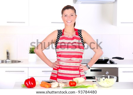 A portrait of a young beautiful wife working in a modern kitchen
