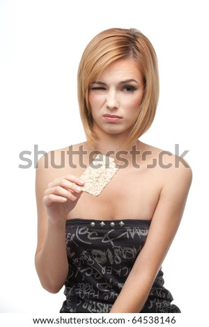 a portrait of a young, blonde woman, holding in one of her hands a slice of bio bread from wich she just had a taste, having a disgusted and sad expresion on her face.
