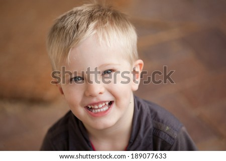 A portrait of a young boy smiling and looking at the camera.  The child looks relaxed and happy. #189077633
