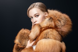 A portrait of a young fashionable woman in a fur coat with a hood. Beauty, fashion.