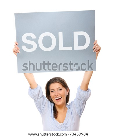 """A portrait of a young happy woman holding a """"sold"""" banner over white background"""