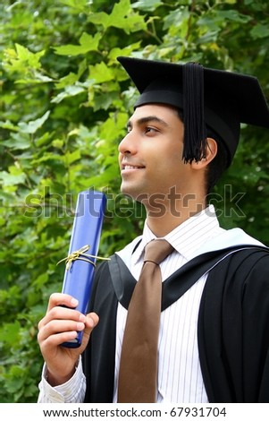 A portrait of a young Indian guy in a graduation gown.