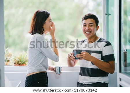A portrait of a young Malay Asian couple enjoying a hot drink and talking to one another fondly during the day by the window balcony. They are both laughing naturally as they share a joke together.