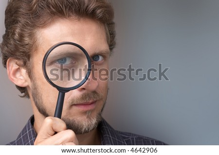 A portrait of a young man with a magnifying glass