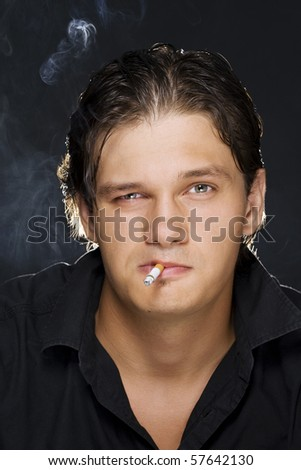 A portrait of a young sexy man smoking a cigarette