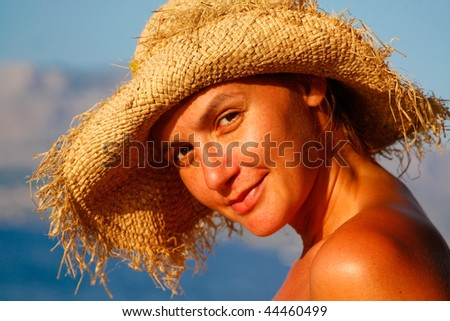 a portrait of a young woman with a straw hat on the beach